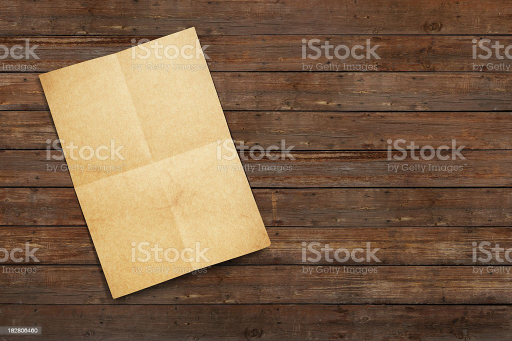 An old paper letter found on a wooden floor Folded old and blank paper on old wooden floor (or table). Ancient Stock Photo