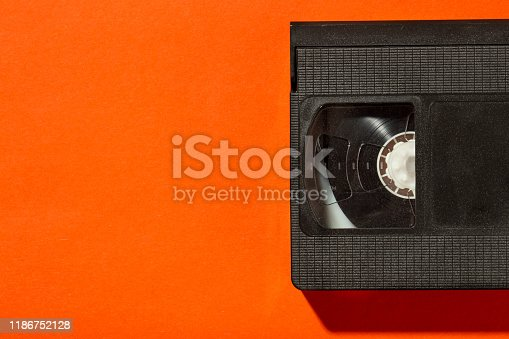 An old plastic video cassette for a film VCR against a bright background. place for text