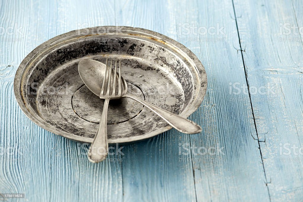 An old plate with fork and spoon stock photo