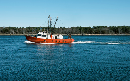Peaceful seascape with a fishing boat passing by over the Cape Cod Canal waterway