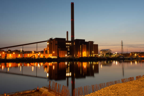 An old red brick powerplant on the waterfront casting reflections on the sea stock photo