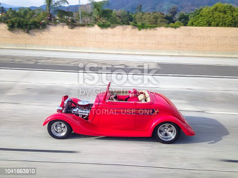 istock An old red car rides on the Los Angeles road. 1041663910