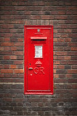 Cambridge, UK - December, 2018. An old red Royal Mail post box in a brick wall. Portrait format.