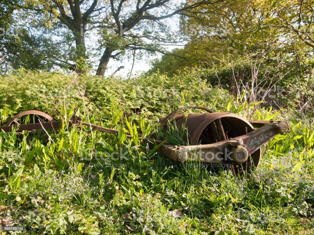 een oude retro verroeste boerderij machine ploegen op de ongebruikte grond royalty free stockfoto