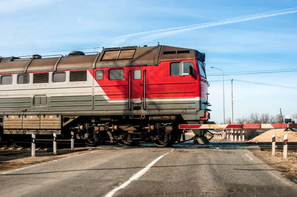 An old russian red train passing across a level crossing, on a small road. stock photo