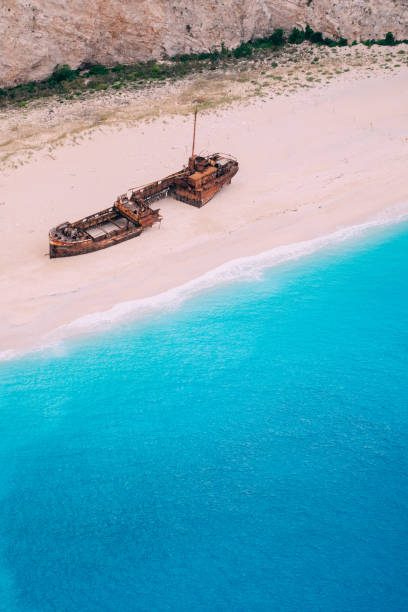 An old rusted ship, wrecked, lies on the seashore. Greece. stock photo