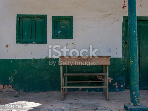 An old school desk left in front of a house at the colonial town of Chiquiza, in the Central Boyacá Province, part of the Colombian Department of Boyacá. The text reads: Bonus 89, in Spanish.