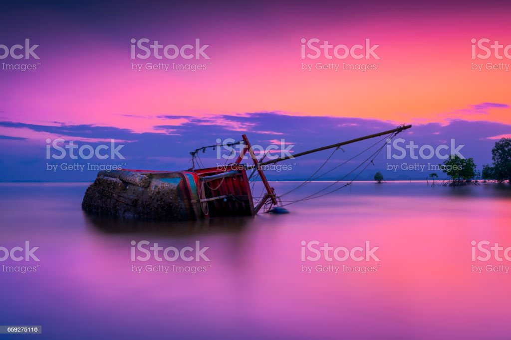 An old shipwreck or abandoned shipwreck, Boat capsized on beach in beautiful sunset background, Thailand. stock photo