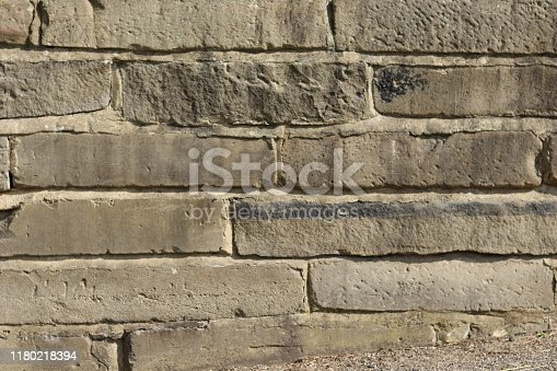 Horizontal stone slabs make up a worn retaining wall.