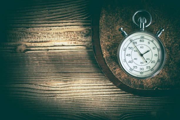 an old stopwatch on a cork background. - stop watch stock photos and pictures