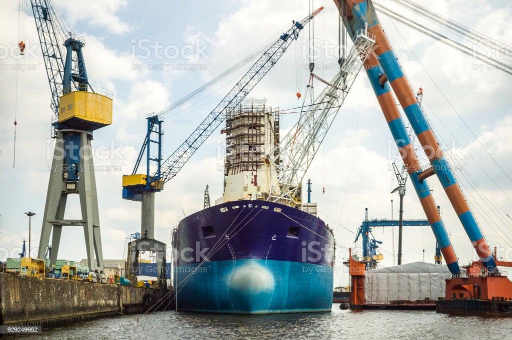 Un viejo petrolero amarrado en un astillero, sometidos a mantenimiento o reparación, rodeado de grandes grúas de elevación - foto de stock