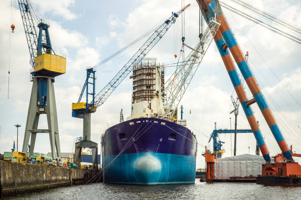 An old tanker moored in a dockyard, undergoing maintenance or repair, surrounded by large lifting cranes stock photo