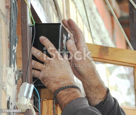 istock An old the electricity counter in the hands of an electrician 1199436682