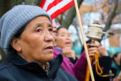 'Washington DC, USA - April 5, 2008: An old Tibetan woman, staring at the Chinese embassy with emotion-filled eyes, is one of several Tibetans protesting against human rights abuses in her homeland. She is holding an American flag, an a woman behind her is spinning a Tibetan prayer wheel'