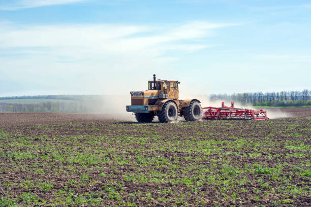 an old tractor is dragging a modern aggregate for tillage leveling the field surface - pillar drill stock photos and pictures