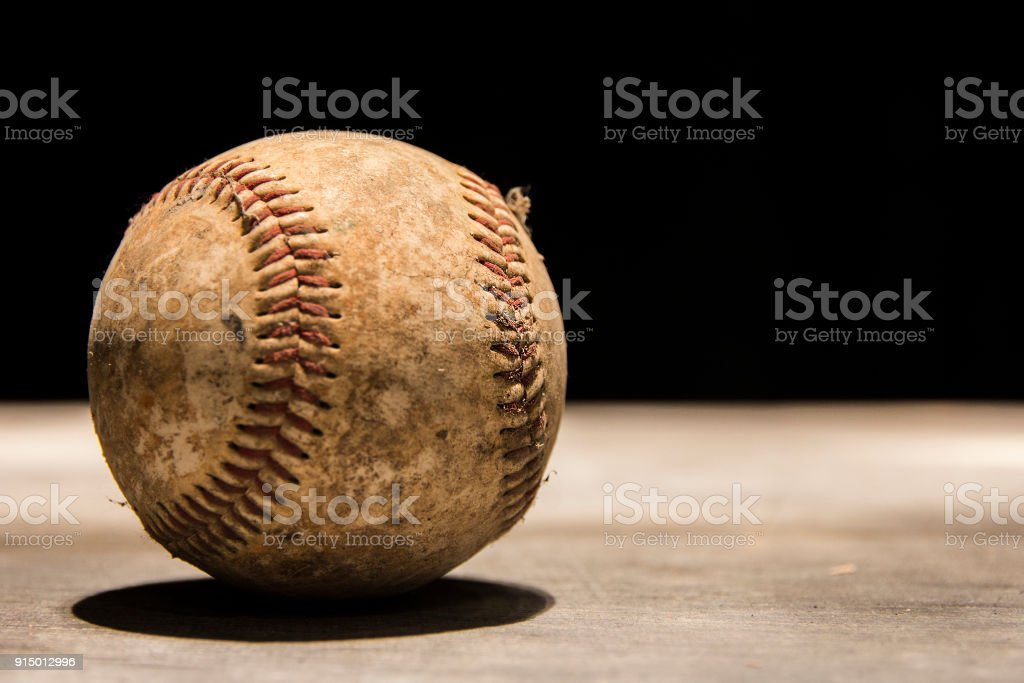 An old, vintage, worn out baseball on a black background. stock photo