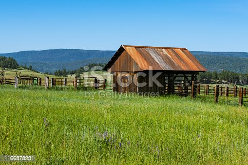 Wooden barn with metal roof in a meadow on a ranch near Pagosa Springs, Colorado