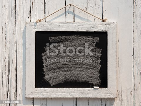 An old white weathered teak wooden framed blackboard with a white chalk swash, hangs from an old rusty nail by old rope against an old white weathered teak wood panel wall background. Good copy space with lots of rustic character.