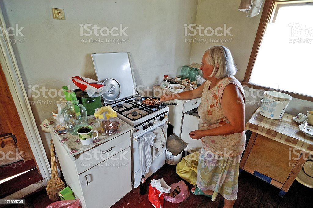 An old woman cooking in her kitchen stock photo