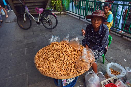 An old woman sells peanuts
