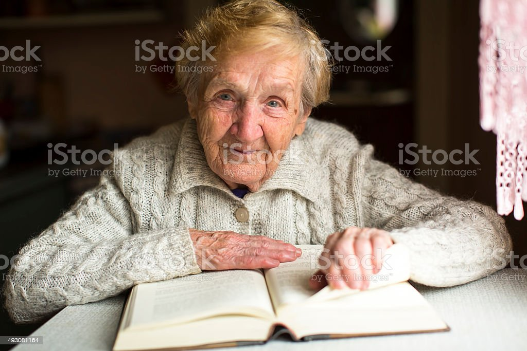 An old woman sitting with a book at the table. stock photo