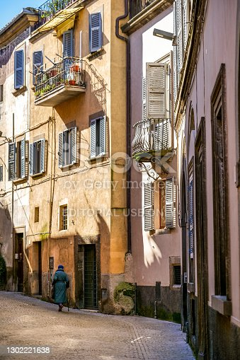 Viterbo, Italy, February 11 -- An old woman walks along a suggestive alley in the historic center of Viterbo, the capital of the ancient Tuscia region. This charming medieval town stands on the route of the ancient Via Francigena which in medieval times connected the regions of France to Rome up to the commercial ports of Puglia to reach the Holy Land. Image in High Definition format.