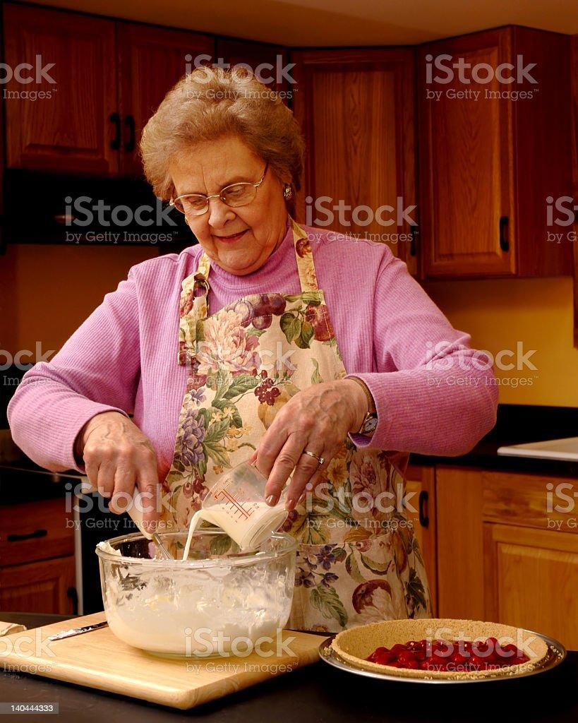 An old woman wearing an apron making a dessert stock photo