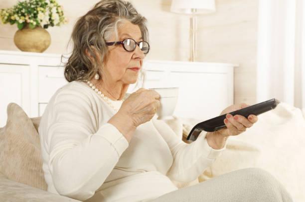 Una anciana con un control remoto de TV en la mano - foto de stock