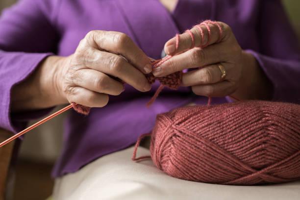 an old women knitting - lavorare a maglia foto e immagini stock
