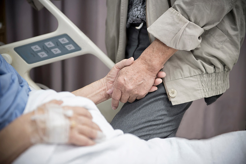 1049772134 istock photo An old women Sick patient lying on bed holding her husband hand in hospital for medical background.Healthcare and Medical for elder concept. 1163494987