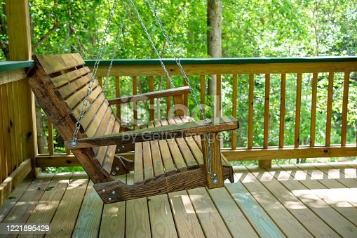 An old wooden bench swing hangs from chains on a newly built open-air porch. Concept of relaxation.