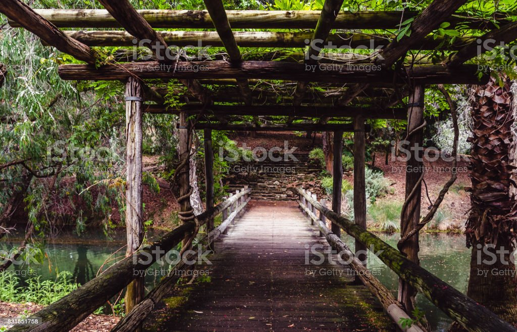 An Old Wooden Bridge over a Stream in a Park stock photo