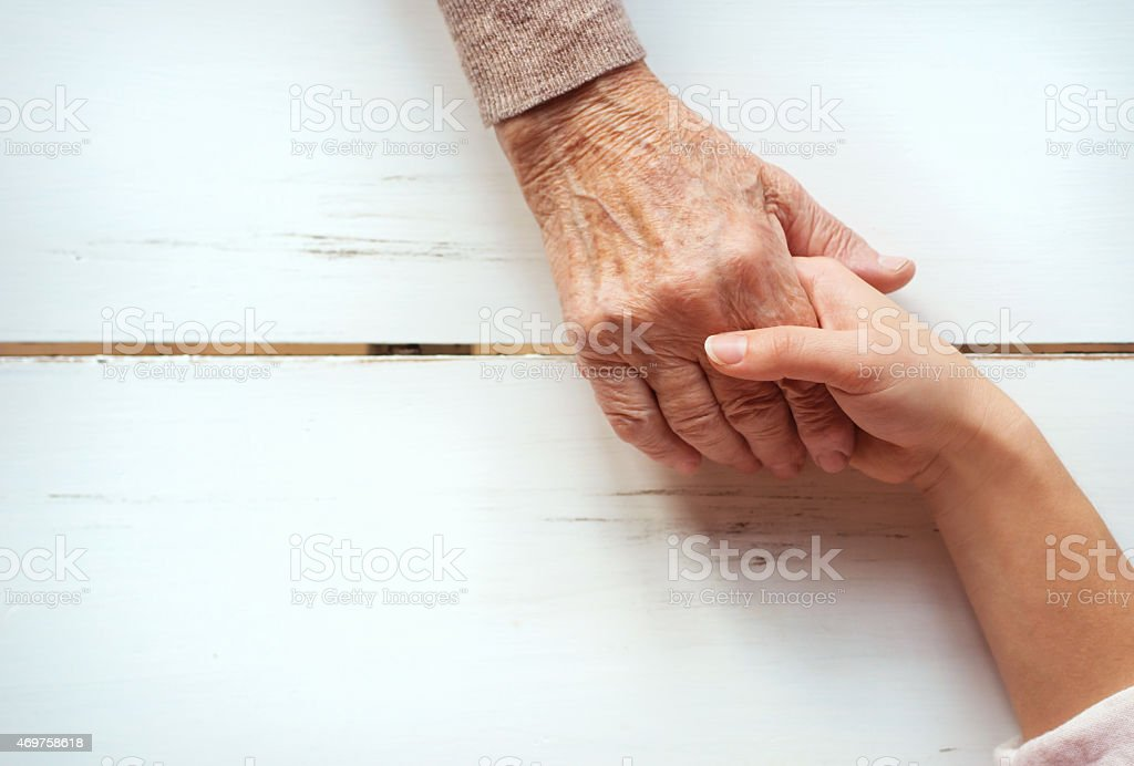 An older and a younger hand holding on a wooden table stock photo