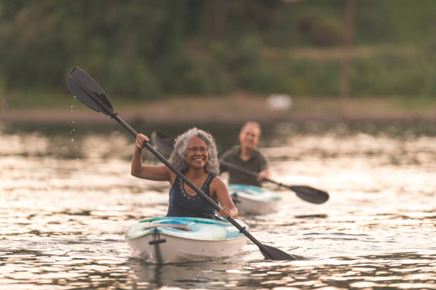an older couple enjoy a late evening of kayaking on the river - kayaking stock pictures, royalty-free photos & images