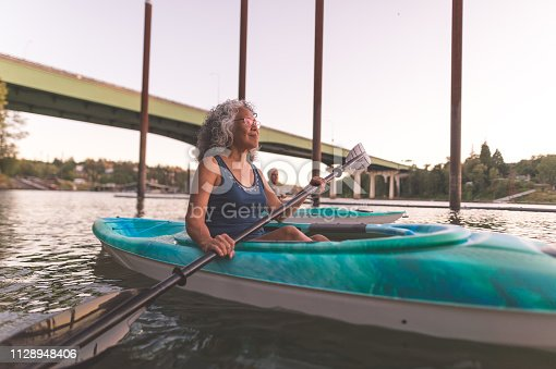 986720410 istock photo An older couple enjoy a late evening of kayaking on the river 1128948406