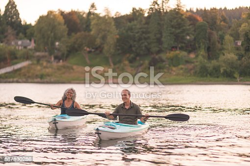 690538774 istock photo An older couple enjoy a late evening of kayaking on the river 887830286
