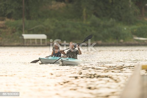 690538774 istock photo An older couple enjoy a late evening of kayaking on the river 887830300