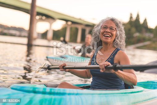 690538774 istock photo An older couple enjoy a late evening of kayaking on the river 887830304