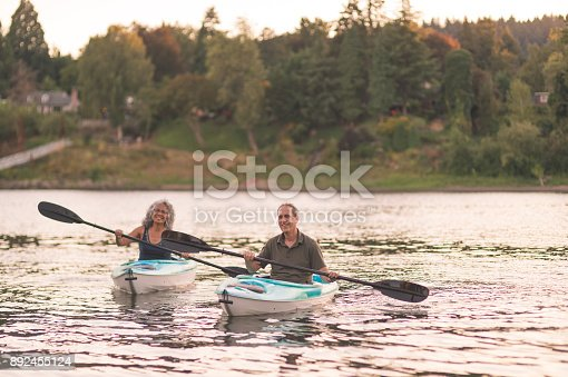 690538774 istock photo An older couple enjoy a late evening of kayaking on the river 892455124