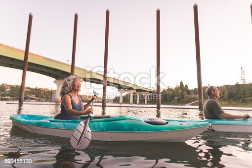 690538774 istock photo An older couple enjoy a late evening of kayaking on the river 892455130
