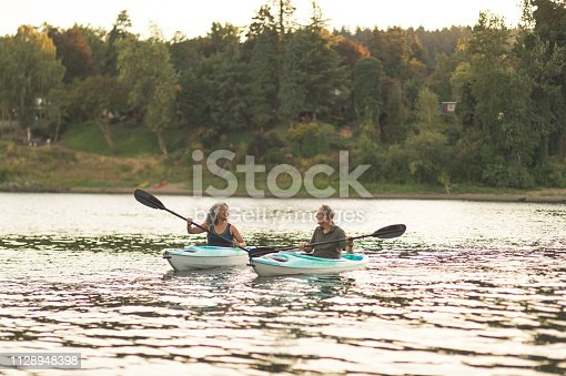 986720410 istock photo An older couple enjoy an early morning of kayaking on the river 1128948398