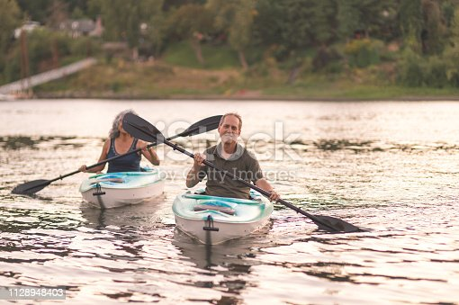 690538774 istock photo An older couple enjoy an early morning of kayaking on the river 1128948403