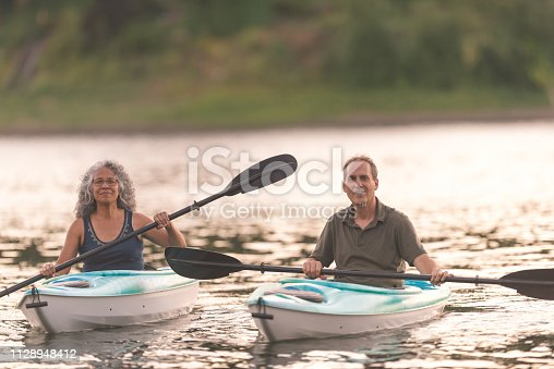 986720410 istock photo An older couple enjoy an early morning of kayaking on the river 1128948412