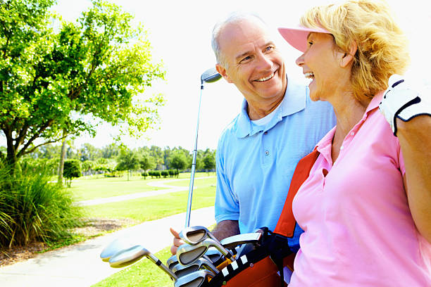 An older couple enjoying a game of golf during the summer stock photo
