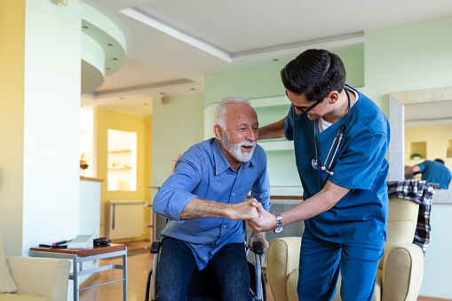 A Careful Caregiver is Helping his Older Disabled Patient in the Living Room and Trying to Help him to Override the Medical Problems and to Get Up From Wheelchair.