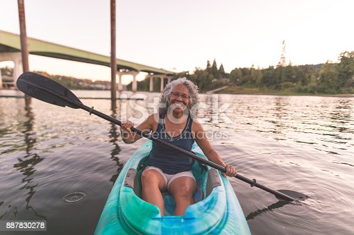 690538774 istock photo An older ethnic woman enjoys an evening of river kayaking 887830278