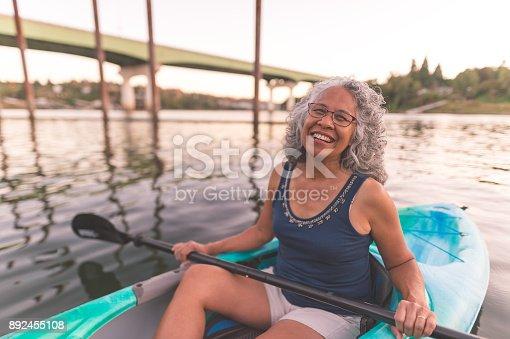 690538774 istock photo An older ethnic woman enjoys an evening of river kayaking 892455108