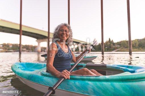 690538774 istock photo An older ethnic woman enjoys an evening of river kayaking 892455114