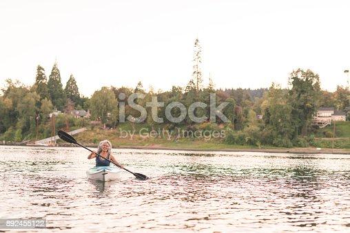 690538774 istock photo An older ethnic woman enjoys an evening of river kayaking 892455122