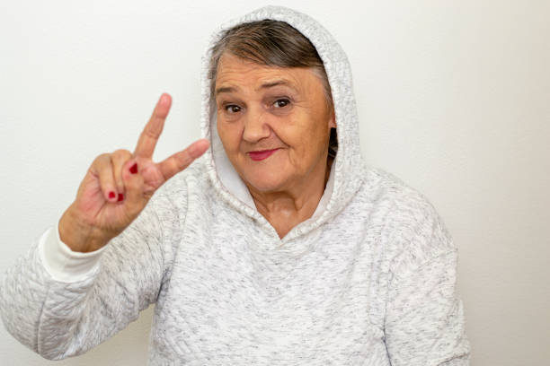 An older hipster woman. Nice shot of a gangster grandma. The old woman dressed in the style of hip-hop, her mood is elated.The old woman shows a peace sign. stock photo